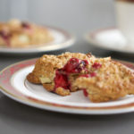 scone broken apart showing juicy cranberries on a red rimmed china plate