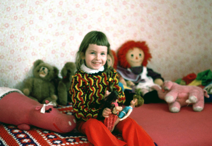 Me at about age 4, sitting on a bed of toys with barbies in hand, waiting for Dad's spaghetti dinner to be ready!