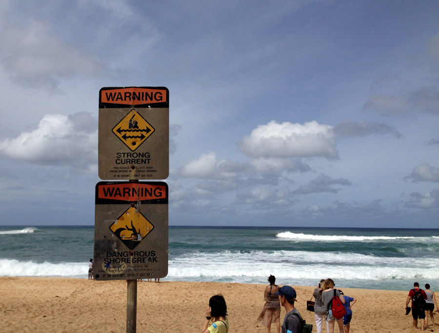 danger signs on beach with high waves in Hawaii