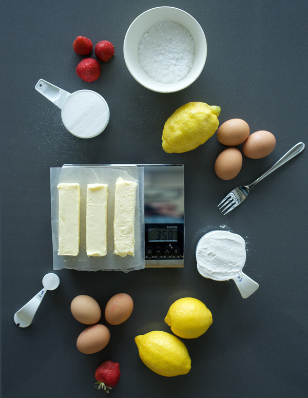 Ingredients set out for lemon squares: butter, sugar, flour, eggs, lemons, berries