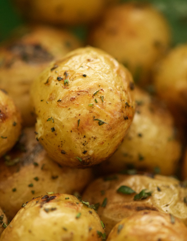 Closeup of golden grilled potatoes, with toasted wrinkly skins seasoned with salt and rosemary