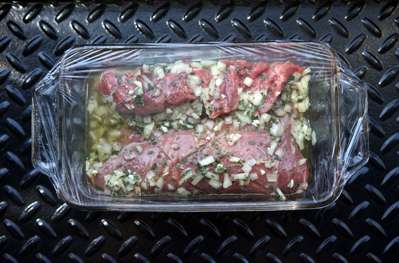 Steak folded into a glass dish to marinate