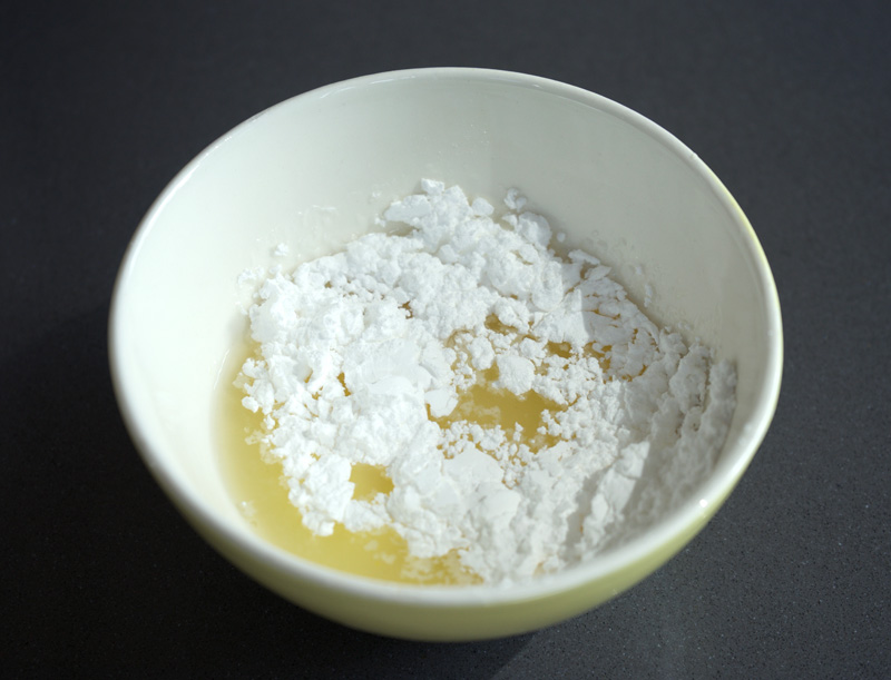 Icing sugar and lemon juice mixing in bowl