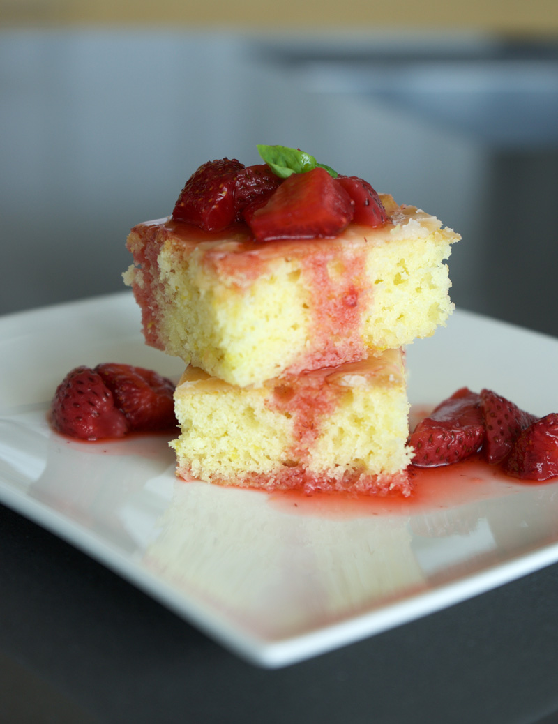 2 cake squares topped with strawberry basil compote, with juices soaking into the cake