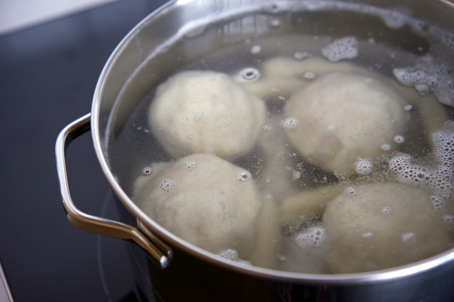 Dumplings cook in gently simmering water
