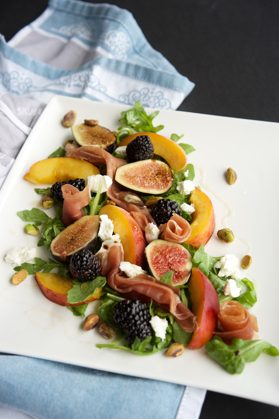 Salad ingredients all put together in a pretty arrangement showcasing the peaches, figs, blackberries, arugula, pistachios and honey drizzle.