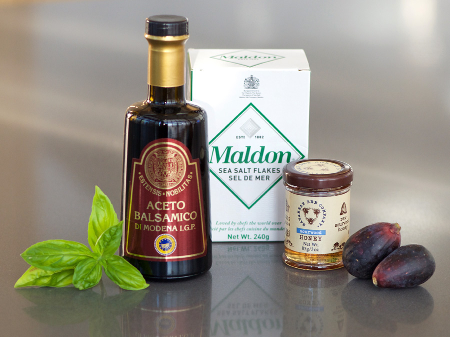 Fresh basil sprig, bottle of Aceto Balsamico Di Modena I.G.P., Malden sea salt and Savannah Bee Company raw Sourwood honey