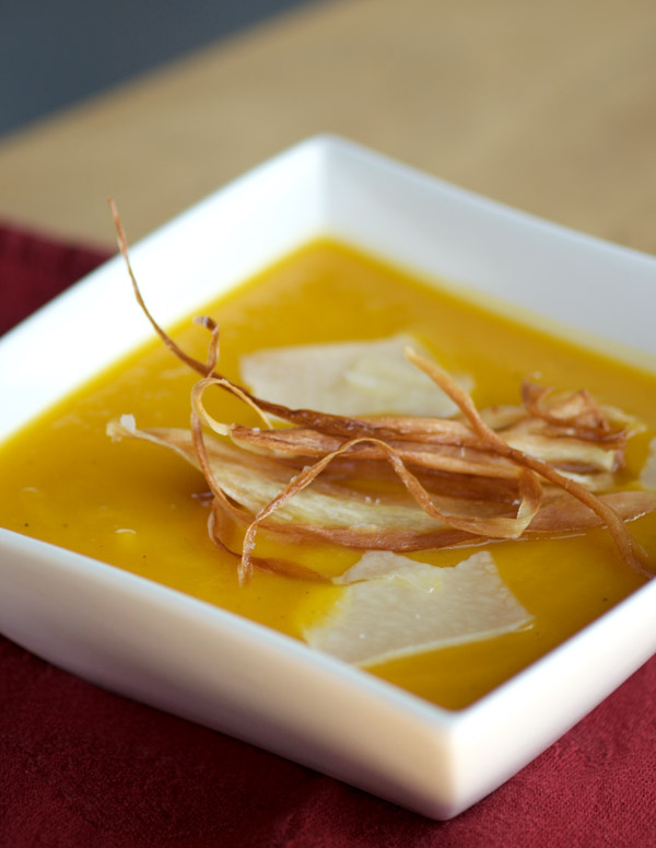 Bowl of glorious golden soup topped with Parmigiano Reggiano cheese and parsnip chips