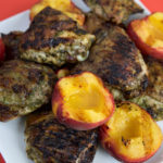 Grilled pesto chicken with peaches piled onto a plate