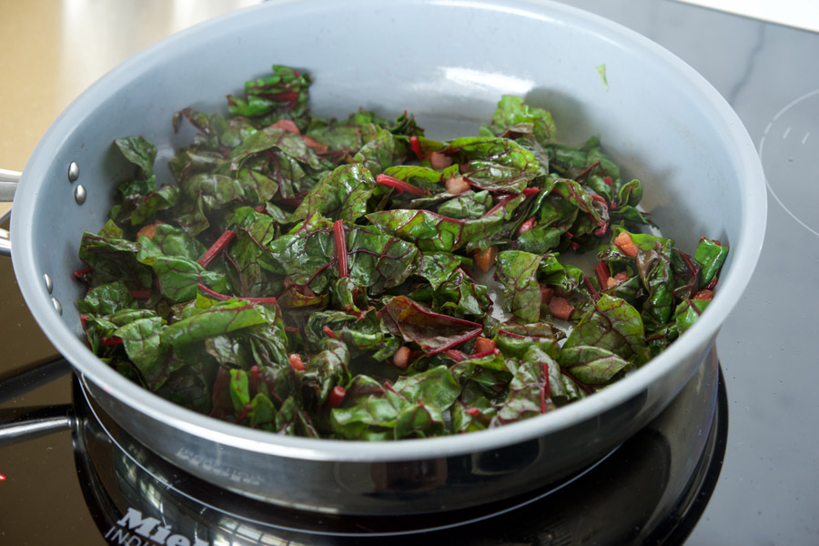 Swiss Chard fills a saute pan, steam rises