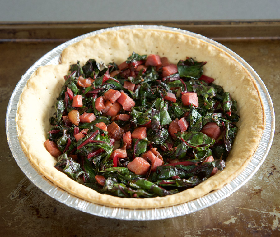 Swiss chard and pancetta line the bottom of the crust