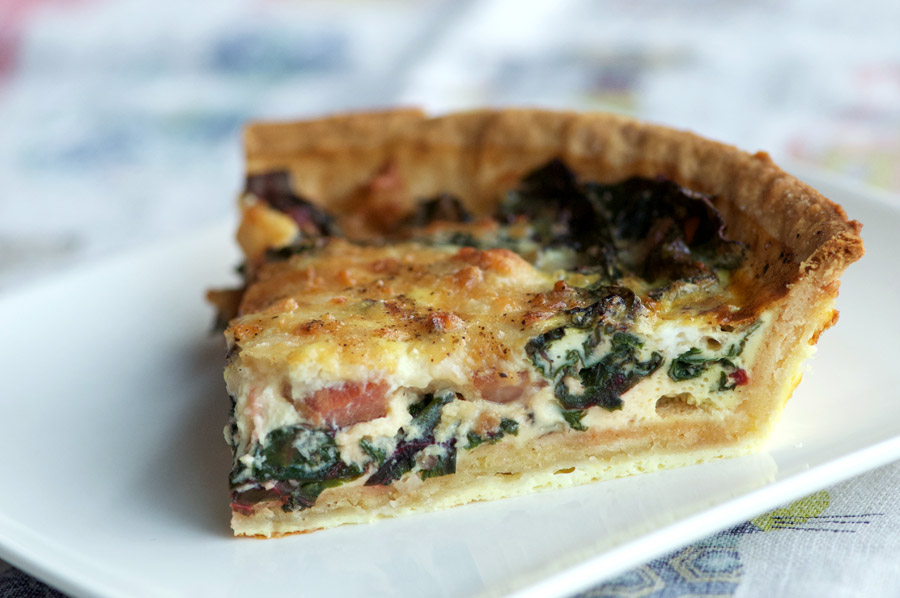 slice of quiche studded with pancetta and swiss chard