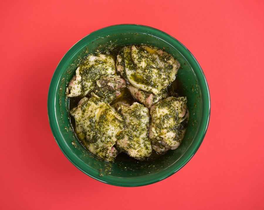 Chicken thighs marinating in pesto in a green bowl on bright pink backgorund