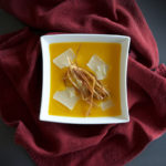 Plated butternut soup with parsnip chip garnish on a deep red cloth