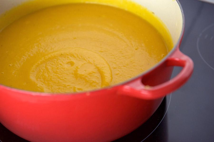 thick swirls of rich orange butternut squash soup in a red pot