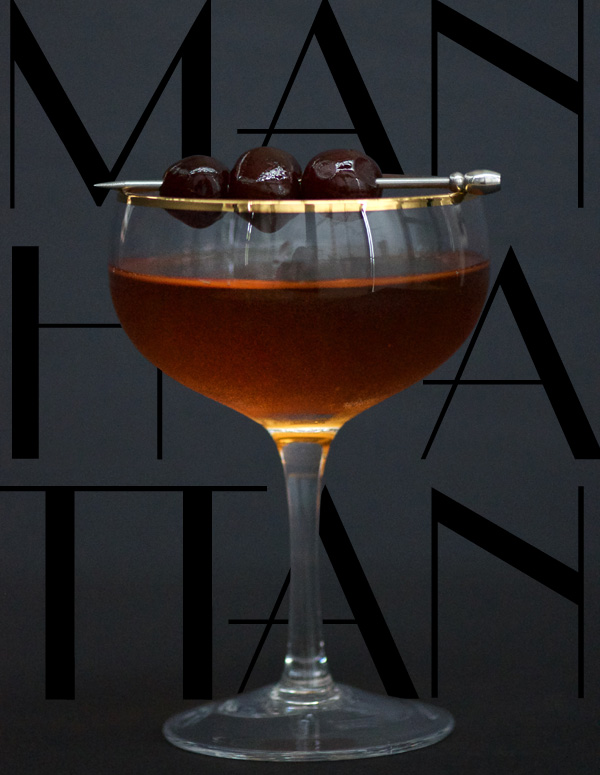 Elegant Barrel Aged Manhattan in gold rimmed cocktail glass with bourbon soaked cherries
