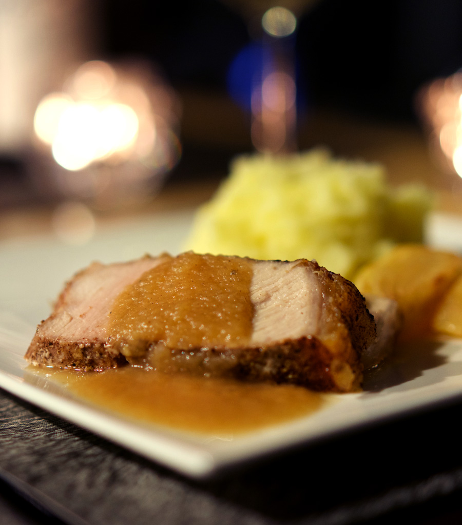 Spiced Pork Roast with Apple Onion Gravy is plated with potatoes and roasted apple slices