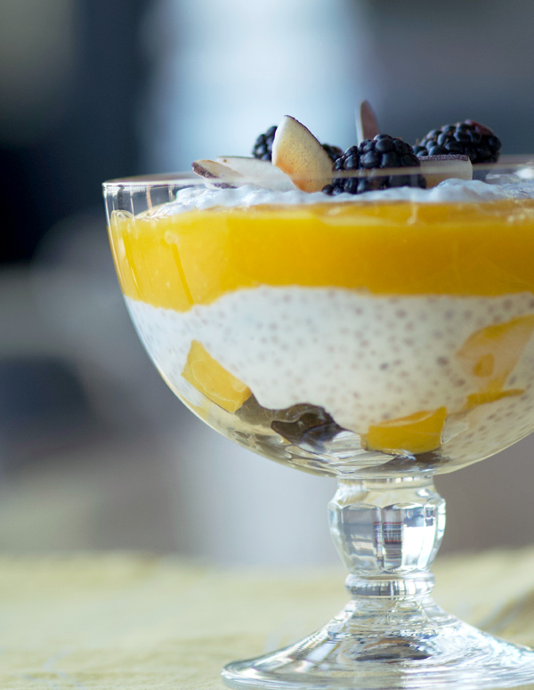 Healthy chia pudding is layered with mango puree and blackberries