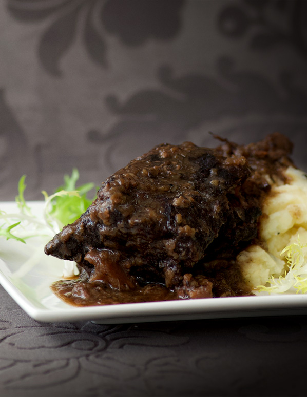 Elegant wine-braised short ribs piled high on fluffy potato parsnip mash
