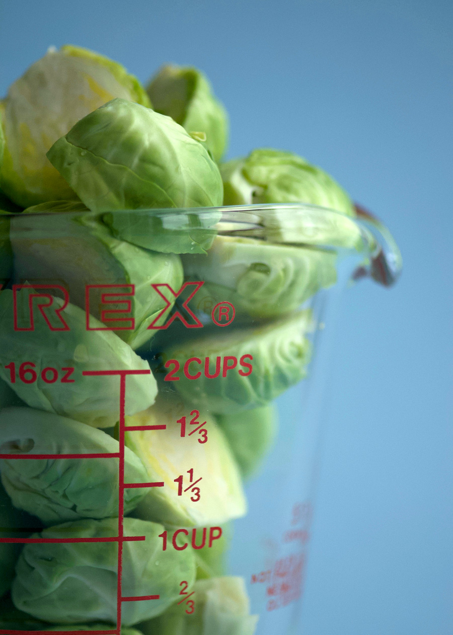 A glass measuring cup brimming with fresh brussels sprouts