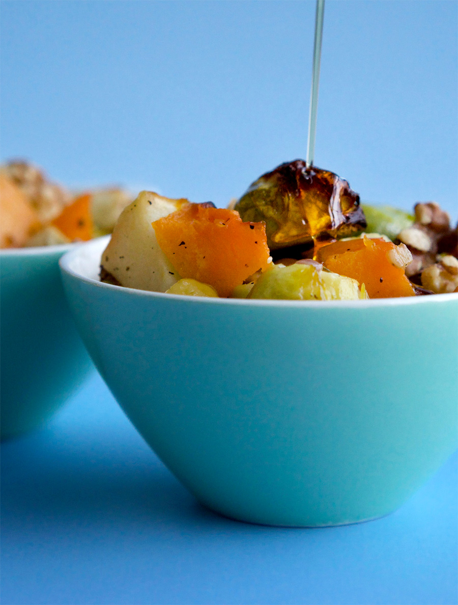 Drizzling maple syrup on roasted brussels sprouts with squash and apples