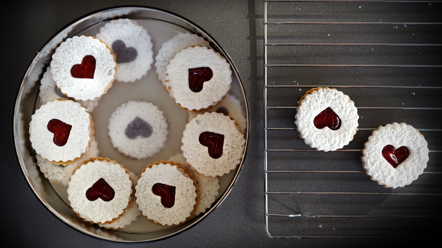 Linzer cookies stored in tin between layers of wax paper