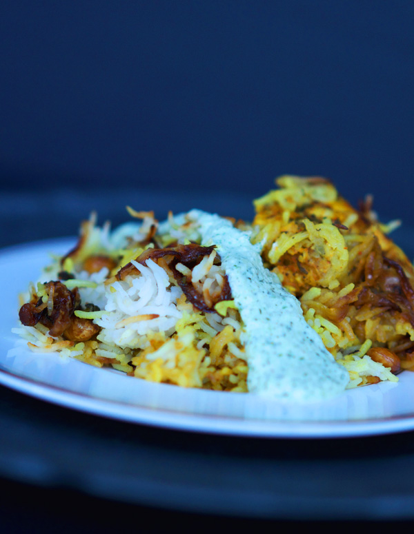 Close up shot of colourful Biryani with cucumber raita.