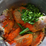 Chicken and bright red and green spices layered in a bowl