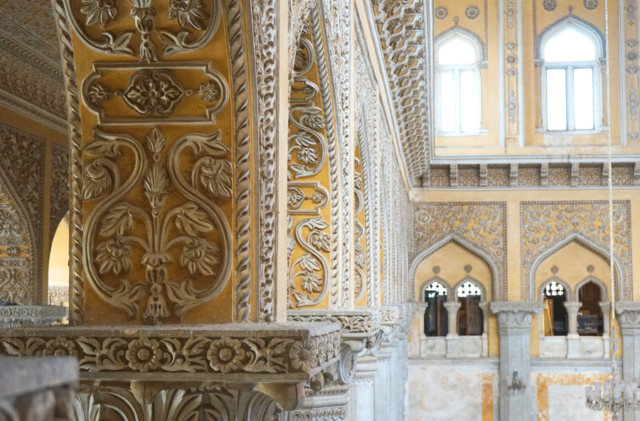 Beautifully intricate details of white relief on yellow inside Chowmahalla palace