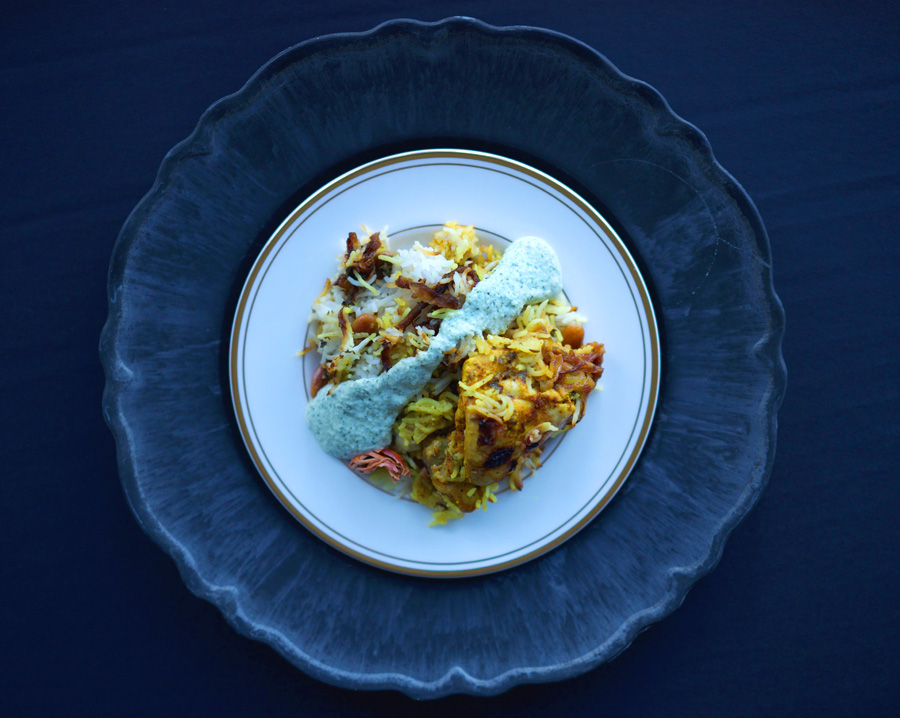 Chicken Hyderabadi Biryani with raita on striking black place setting