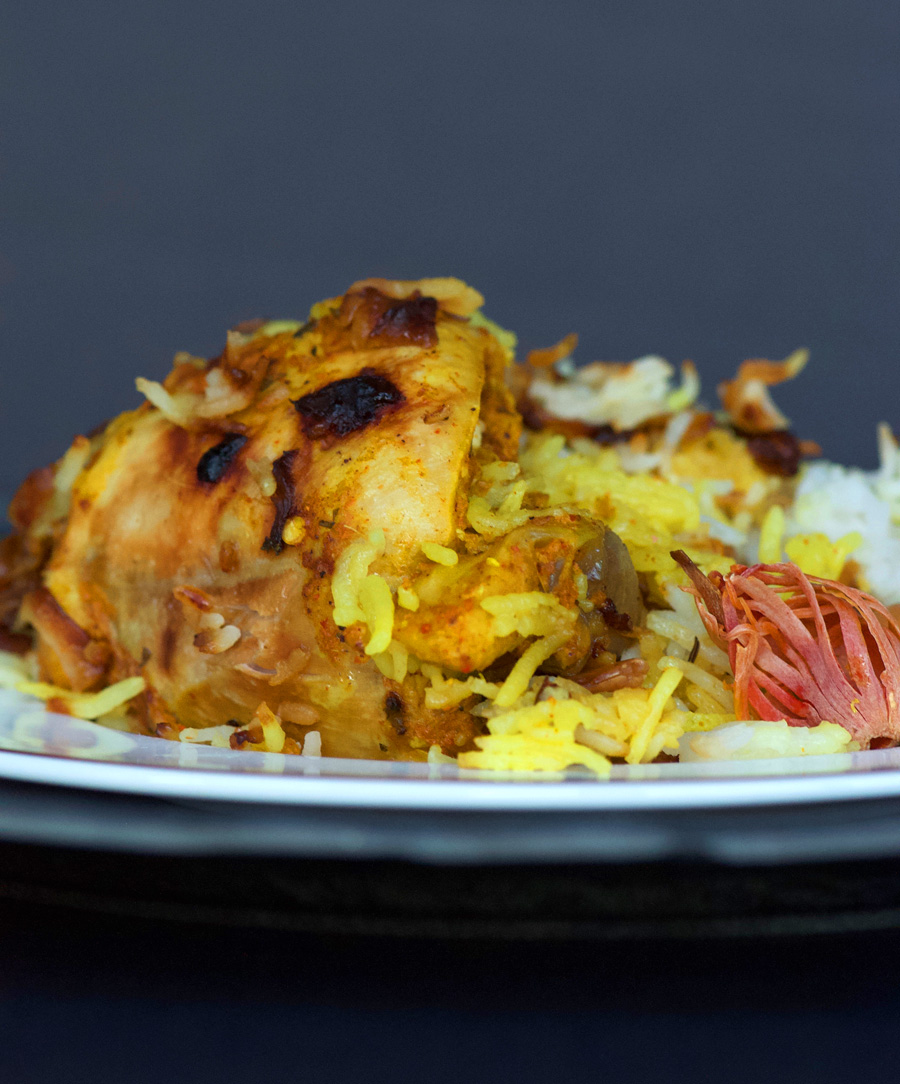 Hyderabadi Biryani with chicken showing colours of saffron, golden shallots and bright mace