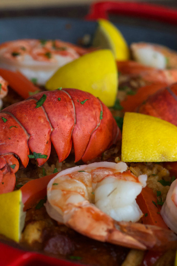 A closeup of the colourful paella with red lobster, yellow lemons and golden rice